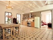 The huge kitchen is in fact the main focus of the apartment, with its high ceilings, open space and french windows looking onto the private patio outside. It even has a sofa. The patio is decorated wi
