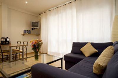 The two bedrooms are furnished with twin beds. The living room, the dining area, and the kitchen share the same space and are all fully equipped with a sofa, television, coffee table, dining table wit